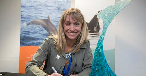 Michaela Strachan holding Orna painted Amaya's whale tail